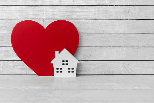 Home Shaped with Red Heart Shaped on white wood over white wood background 1037895408