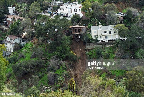 A home sits on the edge of a cliff January 13 2017 in the Hollywood Hills after it's concrete patio was washed away in a mudslide caused by heavy...