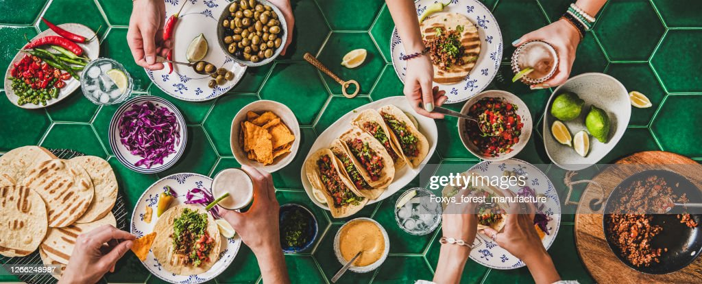 Home taco party with tortillas, tomato salsa and peoples hands : Stock Photo
