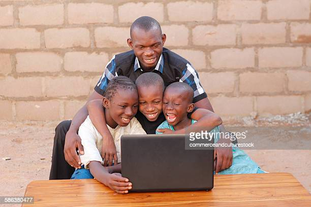 A home teacher with young persons using computer