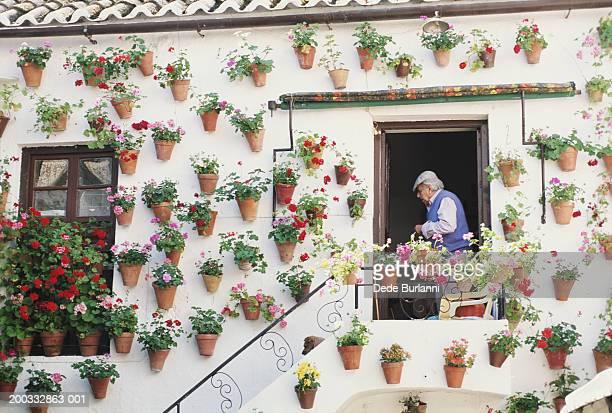 Home with geraniums on exterior, senior man in doorway