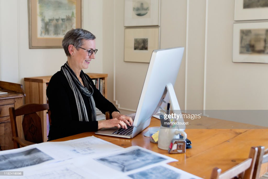 60+ home working professional architect and historian woman : Stock Photo