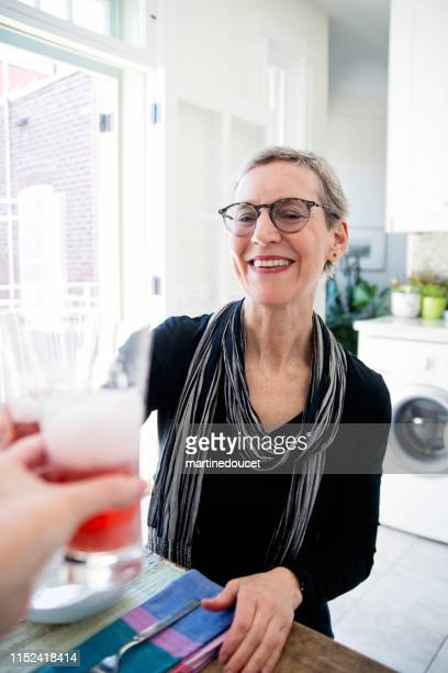 60+ home working professional woman having lunch