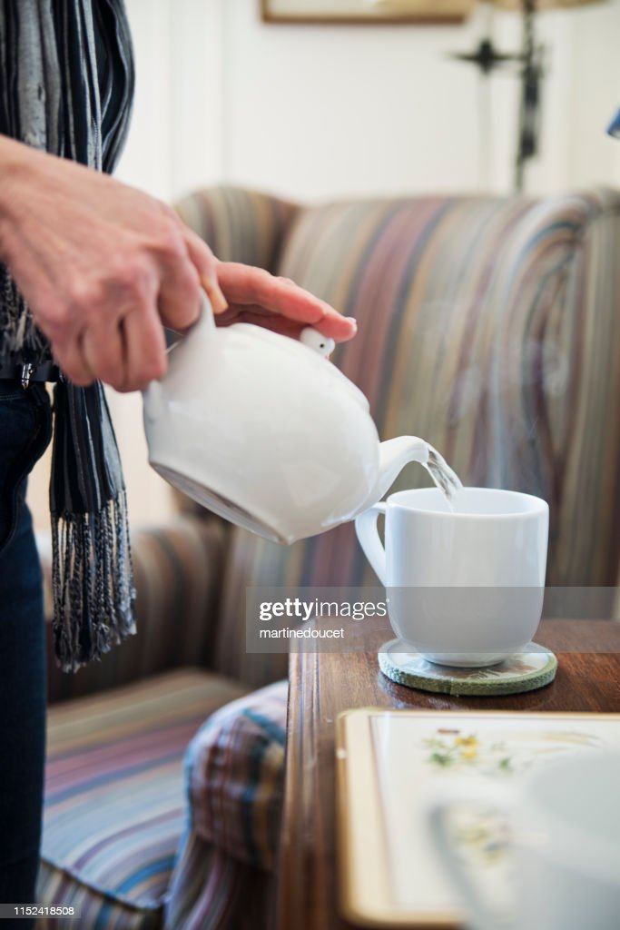 60+ home working professional woman serving tea : Stock Photo