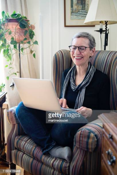 60+ home working professional woman with laptop in living room