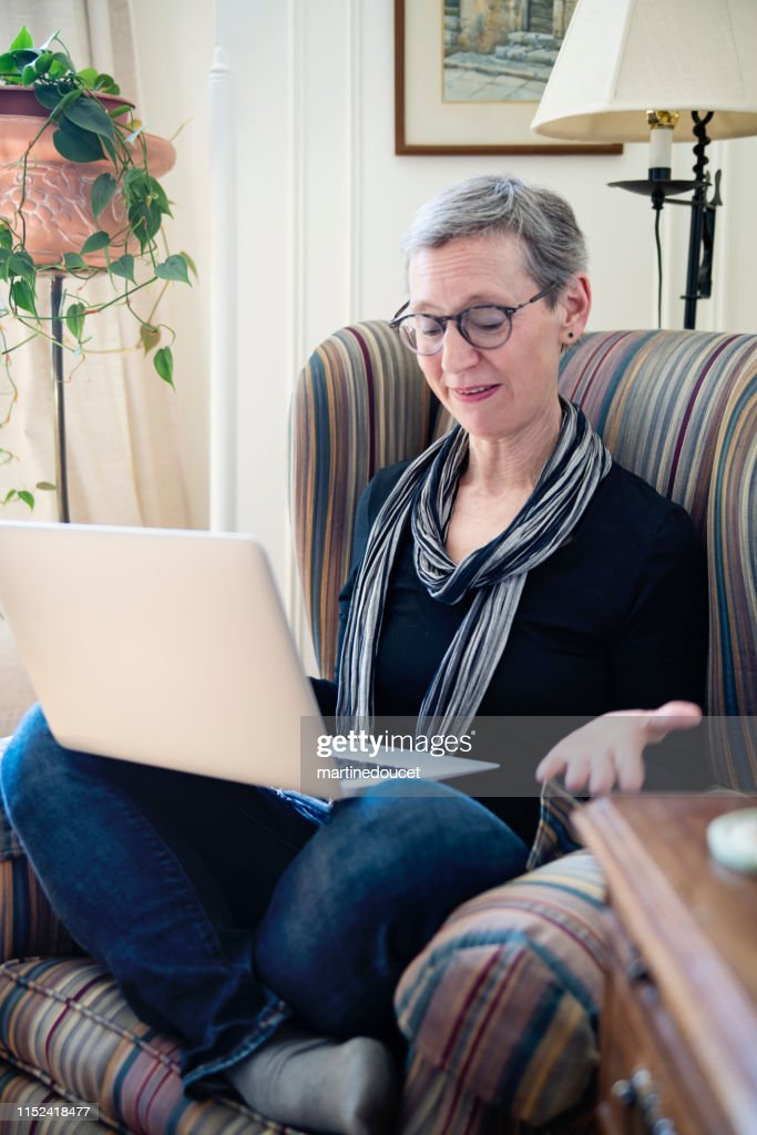 60+ home working professional woman with laptop in living room : Stock Photo