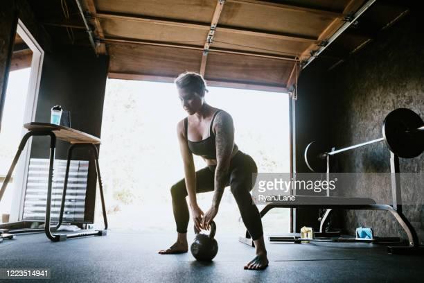 home workout in garage gym - kugelhantel stock-fotos und bilder