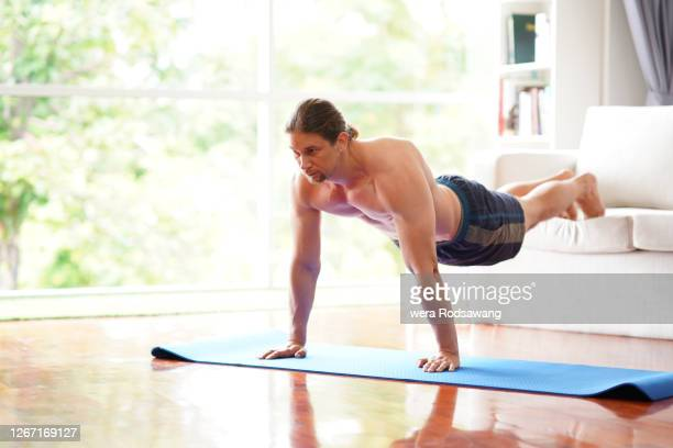 home workout young man poses plank used sofa equipment to support for exercising - muscular build stock pictures, royalty-free photos & images