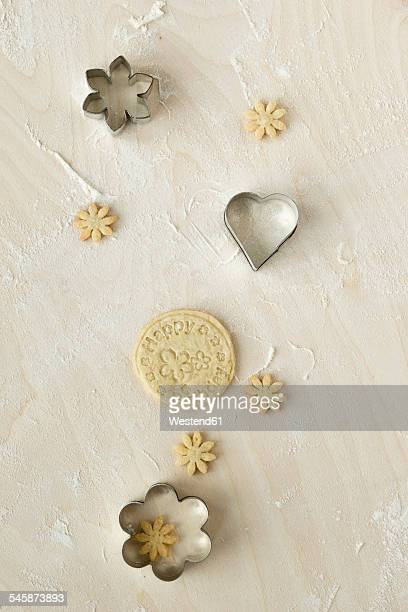 Home-baked birthday cookies and metal cookie cutters on light wood