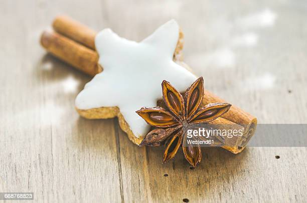 Home-baked cinnamon star, cinnamon sticks and star anise on wood