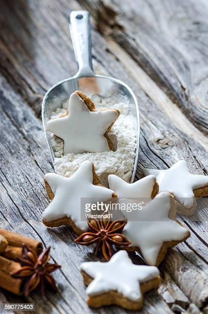 Home-baked cinnamon stars, shovel of flour and spices on wood