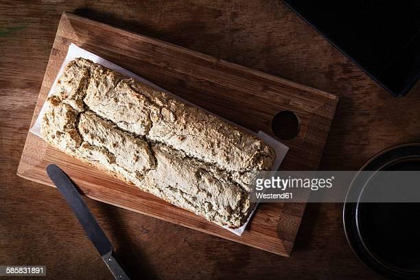 Home-baked wholemeal bread, gluten-free, bread knife on chopping board