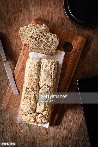 Home-baked wholemeal bread, gluten-free, bread knife, slices of bread on chopping board