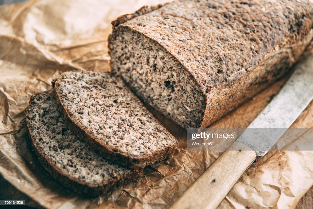 Home-baked wholemeal glutenfree bread and bread knife on brown paper : Stock Photo