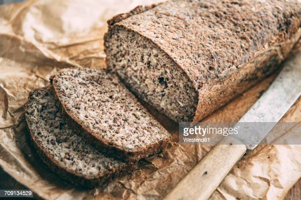 Home-baked wholemeal glutenfree bread and bread knife on brown paper