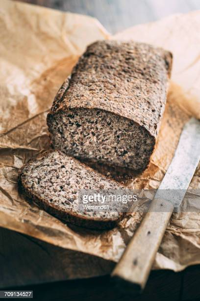 Home-baked wholemeal gluten-ree bread and bread knife on brown paper