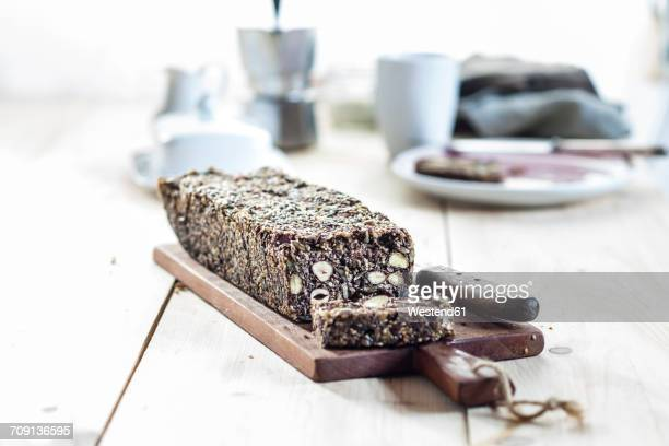 Home-baked wholemeal gluten-ree bread with nuts and seeds on wooden board
