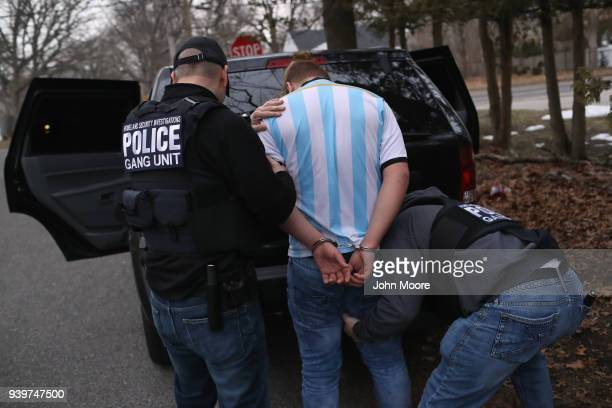 Homeland Security Investigations ICE agents frisk a suspected MS13 gang member and Honduran immigrant after arresting him at his home on March 29...