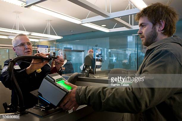 A Homeland Security officer instructs a traveler as he is fingerprinted using the new biometric scanner at the JFK International Airport in New York...