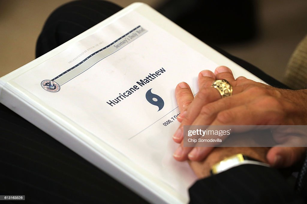 U.S. Homeland Security Secretary Jeh Johnson holds his briefing book about Hurricane Matthew while meeting with President Barack Obama in the Oval Office at the White House October 7, 2016 in Washington, DC. The hurricane is now a category 3 and is headed for Florida after wreaking havoc in Haiti, Cuba and the Bahamas.