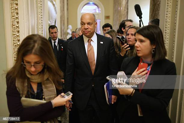 Homeland Security Secretary Jeh Johnson is surrounded by reporters as he moves between meetings with senators at the US Capitol February 3 2015 in...