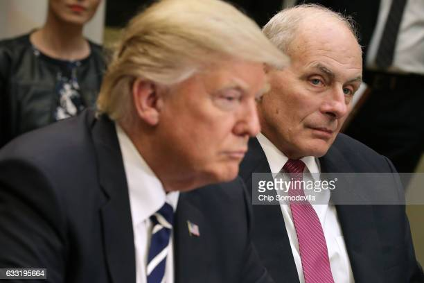 Homeland Security Secretary John Kelly listens as US President Donald Trump delivers remarks at the beginning of a meeting with government cyber...