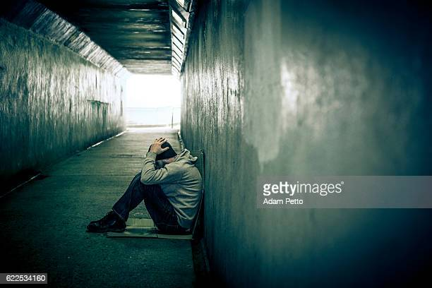 homeless adult male sitting in subway tunnel, hands on head - homeless stock photos and pictures