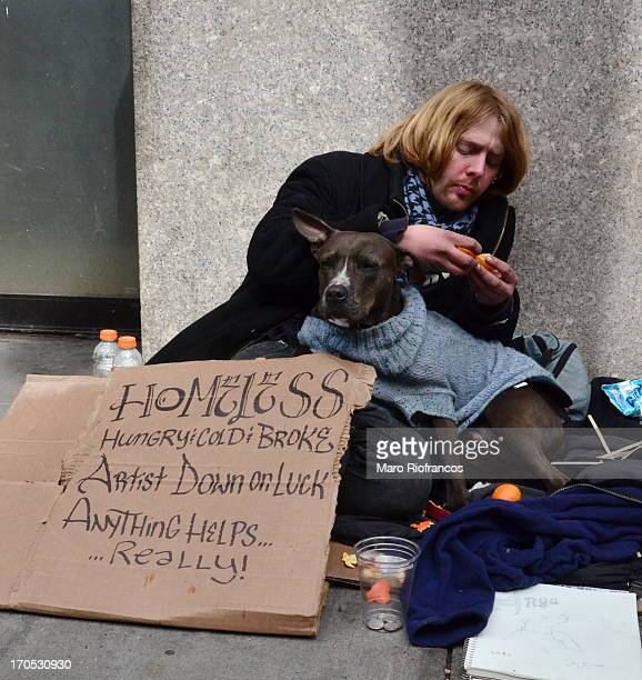 Homeless artist sitting on the sidewalk in Manhattan, near 23rd and 5th Ave., with his dog in a sweater and a sign asking for money.