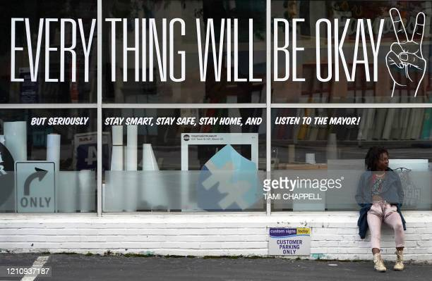 Homeless aspiring singer Ebony Tymes sits by a business window displaying a Everything Will Be Okay message on Peachtree St in Atlanta Georgia on...