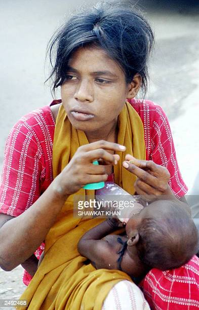 A homeless Bangladeshi mother sits with her child at the side of one of the main roads in Dhaka 07 September 2003 Every day thousands of people...