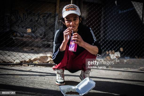A homeless boy drinks his juice and eats his meal distributed by volunteers in Bogota Colombia on December 15 2017 Homeless people who are called...
