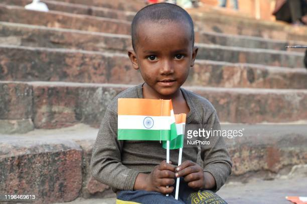 A homeless boy holds the Indian National Flag as he sits on the stairs of Jama Masjid in the Old Quarters of Delhi India on 26 January 2020