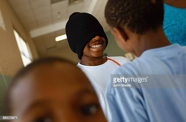 """Homeless boy is blindfolded whhile being led by fellow children in a """"trust walk"""" game at the Center of Hope shelter for homeless women and children..."""