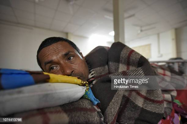 A homeless boy lies on a bed inside a shelter home at Sarai Kale Khan on December 18 2018 in New Delhi India There are some 83 permanent shelters and...