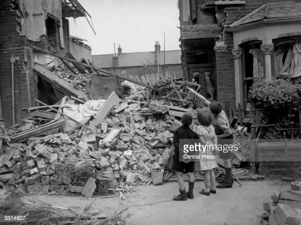 A homeless boy points out his bedroom to his friends after his home had been wrecked during a random bombing raid in an eastern suburb of London
