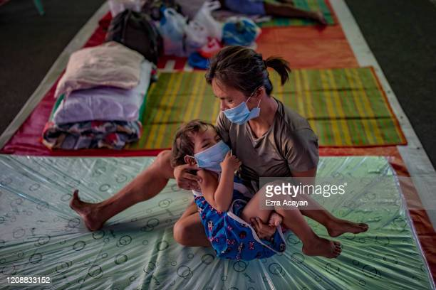 A homeless child and her mother wearing facemasks rest inside a gymnasium converted into a shelter for the homeless who are unable to feed themselves...