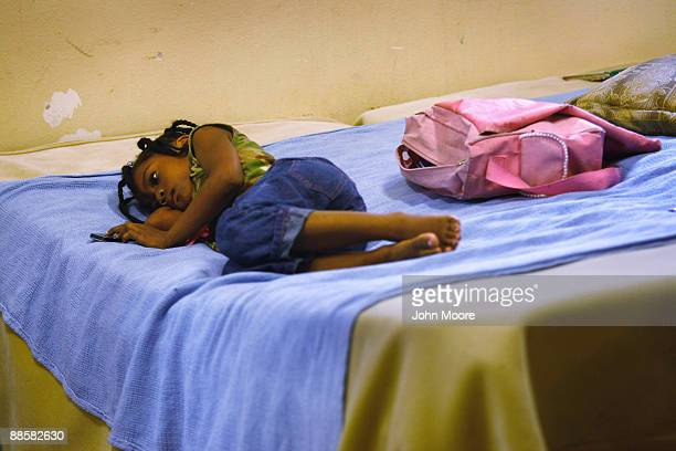 Homeless child Cassandra Martin, age 6, lies on a bed in a common room for recent arrivals to the Presbyterian Night Shelter on June 19, 2009 in Ft....