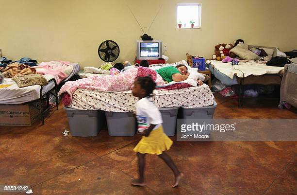 Homeless child runs past as homeless mother Carrie Wilson sleeps at the Presbyterian Night Shelter on June 19, 2009 in Ft. Worth, Texas. Wilson moved...