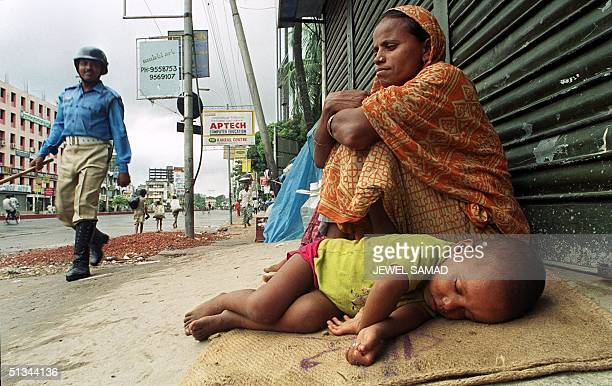 A homeless child sleeps next to his mother in front of a closed shop in Dhaka's Nayapaltan area 30 August 2000 as a policeman passes by during the...