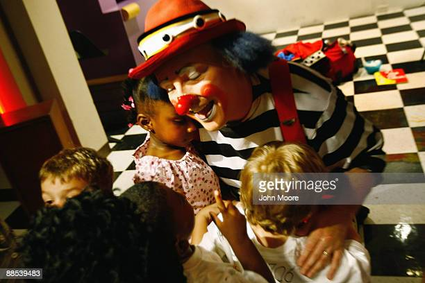 Homeless children hug circus clown Dave Gregg following a free performance at the Dallas Public Library on June 17, 2009 in Dallas, Texas. Dozens of...