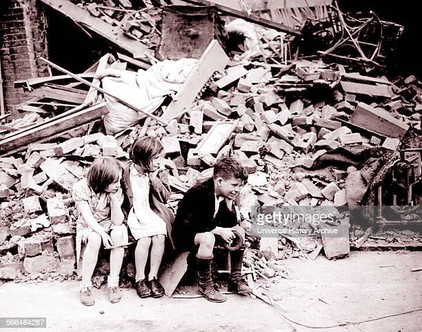 Homeless children sit in front of their wrecked home in London's East End during the blitz of World War Two 1940