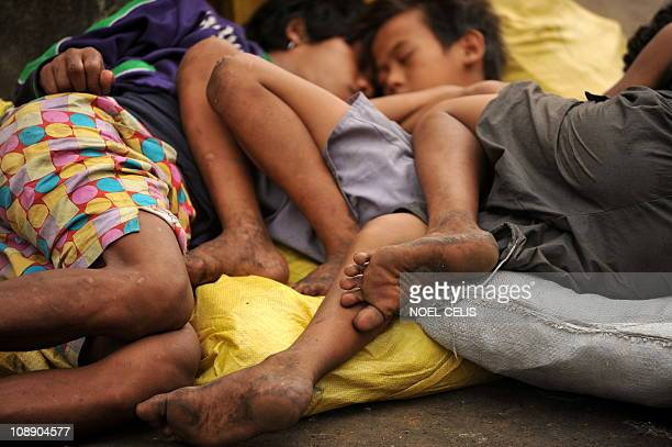 Homeless children sleep at the Divisoria market in Manila on February 4 2011 A third of Philippine school children are stunted because poverty has...