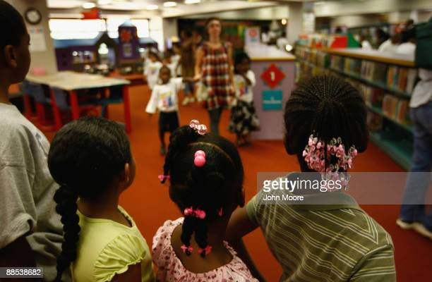 Homeless children watch as other homeless youth arrive to watch a free clown show at the Dallas Public Library on June 17, 2009 in Dallas, Texas. The...