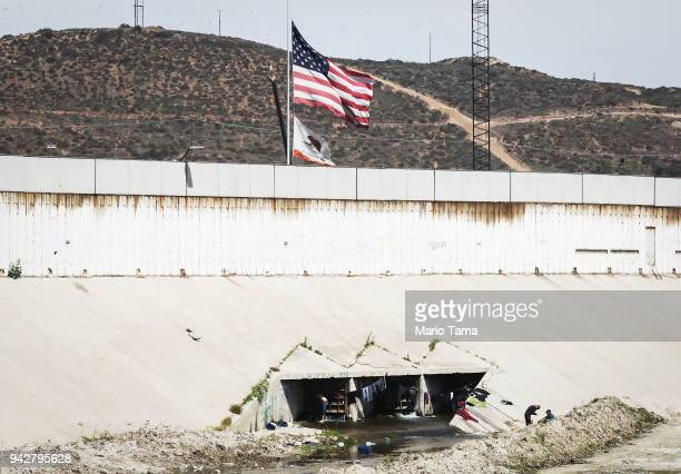 Homeless deportees gather to wash their clothes at a canal along the USMexico border with a border fence and American flag behind them on April 6...
