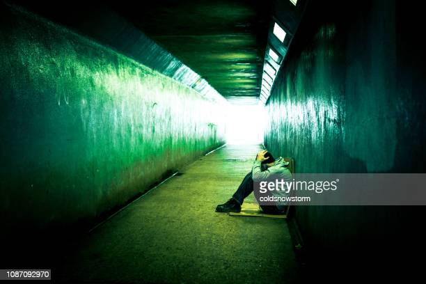 homeless depressed man sitting in cold subway tunnel - drug abuse stock pictures, royalty-free photos & images