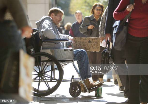 A homeless disabled veteran in his wheelchair is surrounded by pedestrians as he is looking for money along the shopping area known as the...