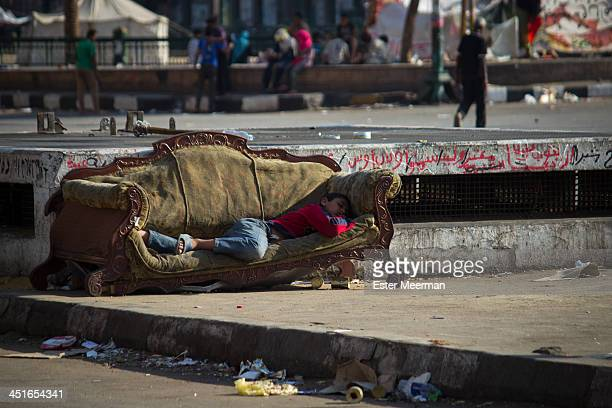 Homeless Egyptian boy sleeps on a sofa on Tahrir square in Cairo, Egypt.