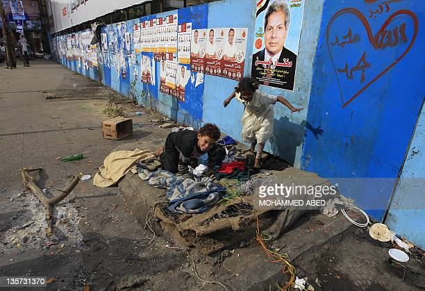 Homeless Egyptian children play near electoral campaign posters in Giza southwest of Cairo on December 13 2011 ahead of the second phase of voting in...