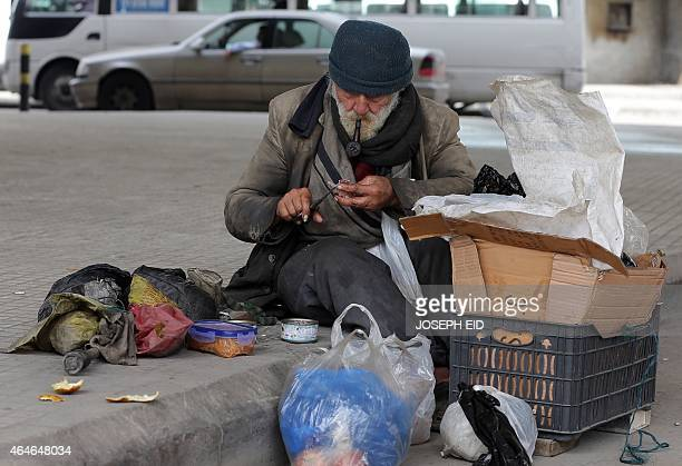 A homeless elderly man smokes a pipe as he prepares his lunch on a sidewalk in the Lebanese capital Beirut on February 27 2015 AFP PHOTO / JOSEPH EID