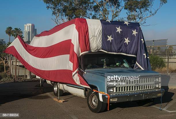 A homeless encampment along Interstate 5 features a truck covered in the American flag on July 23 in San Diego California San Diego with its large...